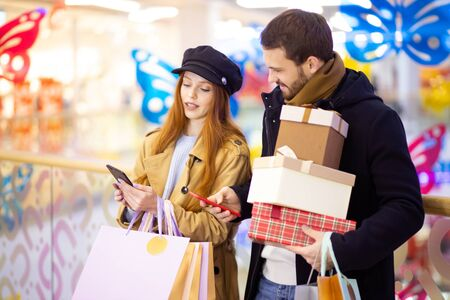 beautiful redhaired woman and bearded young man holding bags and gifts after shopping in mall. leisure time together. young female show at screen of smartphone 写真素材
