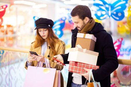 caucasian redhaired woman and bearded man, newly married couple discuss shopping, carrying bags in mall