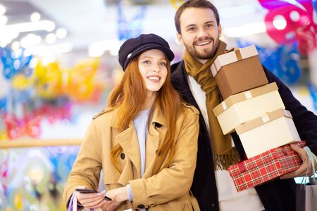 caucasian young couple with gifts and bags after shopping in shop center, redhaired woman and handsome bearded man together 写真素材