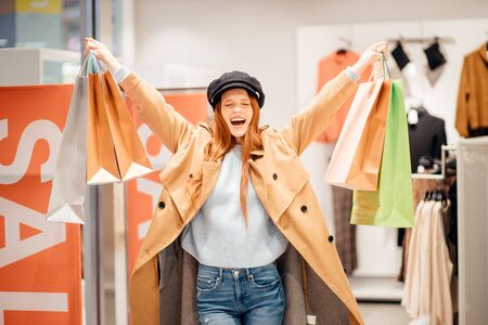 cheerful positive smiling woman with red hair happy after shopping, raised hands holding paper shopping bags.