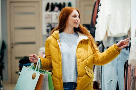 in search of beautiful dress or blouse in shopping store. beautiful redhaired woman wearing yellow coat choosing new outfir in shop 写真素材