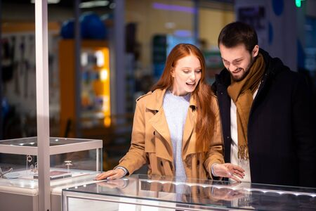 lovely couple choosing expensive golden or silver jewelry at shop, smiling happy female with red hair and bearded man wearing coat 写真素材