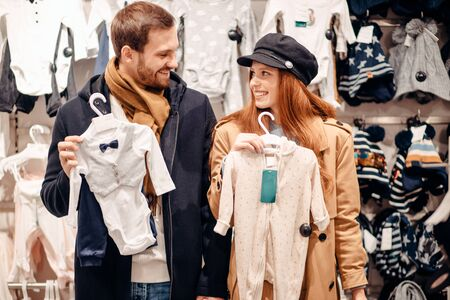 lovely cute couple in search of clothes for future baby in clothes store, look at each other holding babys wear 写真素材