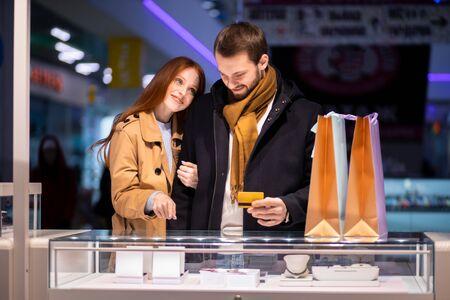 newly married couple, caucasian man and woman during shopping in mall, choose expensive jewelry for female, wearing coat and hugging man 写真素材