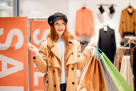 Portrait of beautiful redhaired woman holding shopping bags and excited with discounts in the store