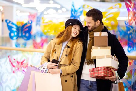 portrait of young caucasian couple adter shopping in mall, center. attractive redhaired female and bearded handsome man together carrying bags 写真素材