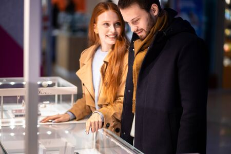 young caucasian couple in shopping, decided to buy jewelry for female in mall.excited redhaired woman and young bearded man together