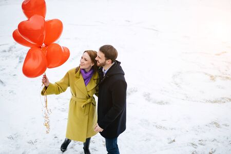 happy caucasian couple spend free time together outdoors, man and woman in coats, with red air balloons in hands. love, relationships concept