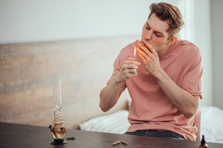 young caucasian man lighting cannabis weed cigarette, going to catch a buzz at home. man leads unhealthy lifestyle, take drugs, marijuana and ganja. smoking treatment, drug treatment Imagens