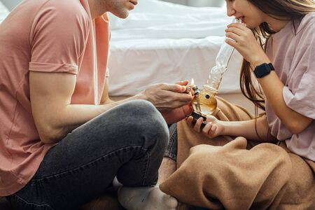 caucasian couple using drugs at home, couple suffer from drug addiction together, use cannabis weed with bong. indoors, sit on the floor catch a buzz Foto de archivo