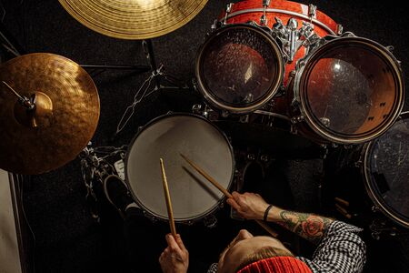 top view on young caucasian man practice playing on drums before concert, he use sticks for playing on drums. professional musician, performer of music. isolated in dark space