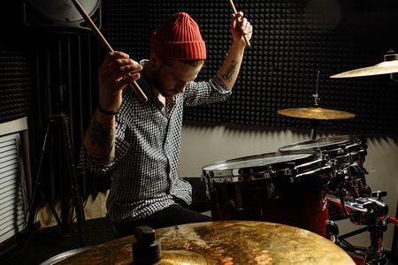 energetic caucasian drummer man professionally play on drums, he enjoy performing music in studio, preparing for concert. rock and roll, music, instruments concept Stockfoto