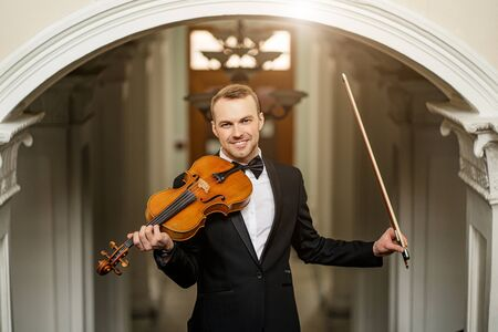 elegant talented professional violinist performing classical music, handsome guy in formal suit holding violin. classical music and instruments concept Stock Photo