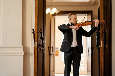 young caucasian talented violinist play violin, handsome guy in formal suit perform classical music, practice before performance
