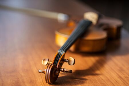 close-up photo of musical instrument violin lying on wooden table. classical music instrument, music concept