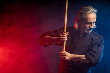 real caucasian mature kendo fighter ready to fight with enemy using bamboo sword shinai . traditional japanese martial art concept, isolated over smoky space