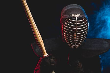 combat warriror, kendo fighter ready to fight using shinai bamboo sword and wearing mask, preparing for competitions. samurai, kendo concept