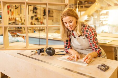 attractive caucasian carpenter lady deals with drawings during work, woman use pencil and ruler before making wooden furniture in workshop