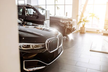 side view on beautiful black cars of business class stand in dealership, waiting for their future owners. automobile, cars. vehicle, dealership concept