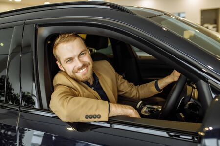 happy caucasian guy made purchase in dealership, he is happy to get a new car. business class car, vehicle, transport, automobile, car concept