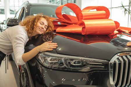 happy caucasian woman hug her new car, enjoy a gift from husband. surprise, emotions, cars, automobile concept