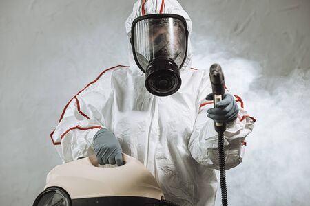 virologist in protective hazmat suit conducts disinfections of surfaces in public and isolated places, pandemic health risk, coronavirus covid-19 concept. spray at camera
