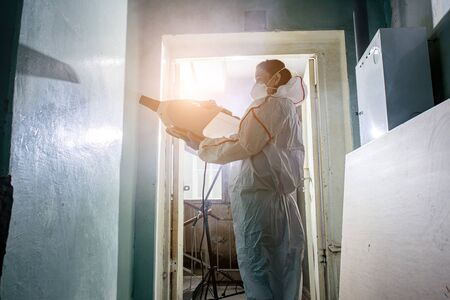 virologist in protective hazmat suit conducts disinfections of surfaces in public and isolated places, pandemic health risk, coronavirus covid-19 concept