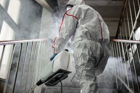 professional disinfector in an NBC personal protective equipment ppe suit, gloves, mask, cleaning isolated space with pressurized spray disinfectant water to remove covid-19 coronavirus