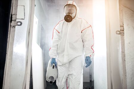 professional disinfector in protective suit holding chemical sprayer and other equipment for sterilization and decontamination of viruses, infectious diseases. coronavirus, COVID-19 epidemic concept Foto de archivo