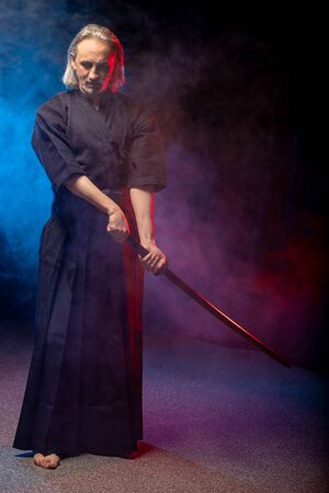 mature caucasian kendo fighter in suit with shinai bamboo sword , practicing fight before competitions. traditional japanese martial art concept. isolated colorful smoky space