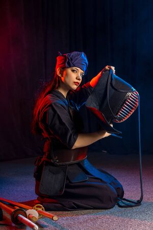 caucasian female keen on kendo activity, combining martial arts practices and values with strenuous sport-like physical activity. wearing special suit and mask, samurai