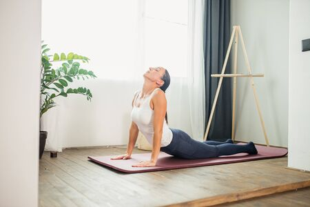 sporty caucasian woman practicing yoga, lying on the floor in Cobra pose, doing Bhujangasana exercise, female in sportswear, leggings and bra working out at home isolated in light room Banco de Imagens