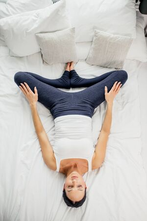 relaxation, meditation. sporty caucasian slim woman in gymnastic costume lying on back, practice shavasana. top view