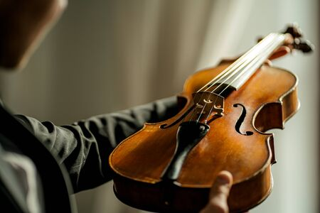 close-up photo of classical instrument violin in male hands. man holding violin before performing music with the use of it