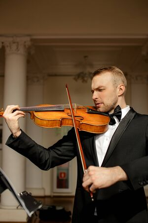 handsome talented violinist in suit play on classic musical instrument, before performance. elegant male in theatre