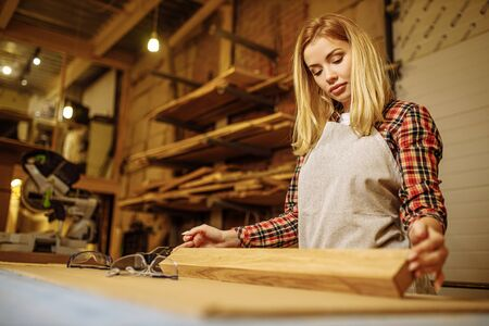 young caucasian professional carpenter woman checking for roughness piece of wood after grinding, female in uniform work in factory