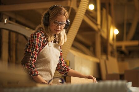 concentrated serious confident carpenter woman deals with piece of wood, she listen to music, protect her ears from noisy sounds in factory