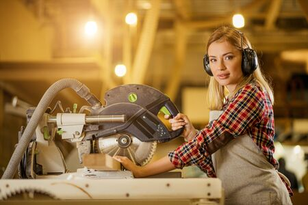 portrait of confident good-looking carpenter woman standing behind electric machine, looking at camera woman enjoy woodworking, she has her own project of making handmade furniture