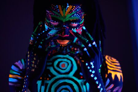 fantastic mysterious african male with UV body art posing at camera, futuristic body art, fluorescent paints glows in neon light