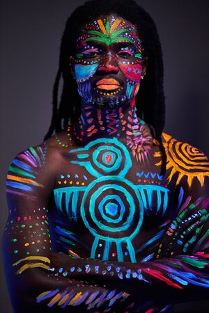 portrait of african man with ethnic pattern, neon makeup in ultraviolet light. fluorescent paints, luminescence prints. body art design of male posing in UV Standard-Bild
