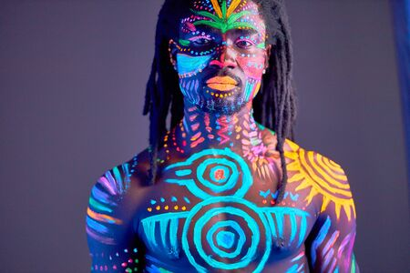 portrait of young black man with colorful ethnic fluorescent prints on his muscular body, shirtless guy posing at camera, colorful makeup and body art