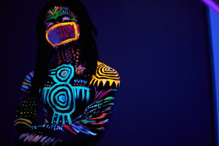 portrait of african male posing with COVID-19 inscription on mask, fluorescent prints glows on neon lights, fight with coronavirus