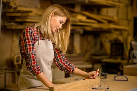 awesome worker of factory. young lady making marks on wooden piece before cutting and drilling it in workshop Banque d'images