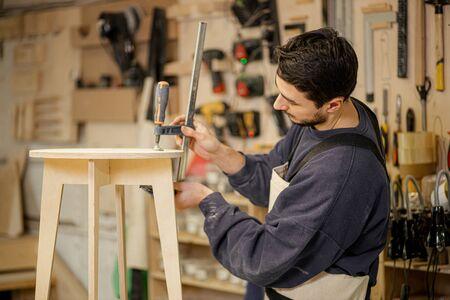 portrait of hardworking carpenter man in uniform making wooden chair on an order, handicraft concept. Stockfoto