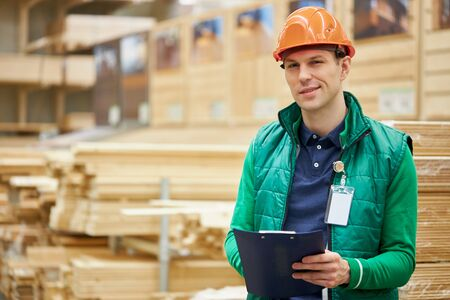 portrait of young caucasian warehouse worker in large warehouse distribution center, a lot of boards in the background, man in uniform