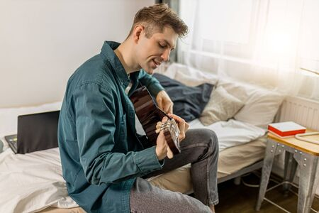 young caucasian guy play acoustic guitar at home, man keen on music, perform music. handsome male in casual wear sit on bed with guitar. indoors