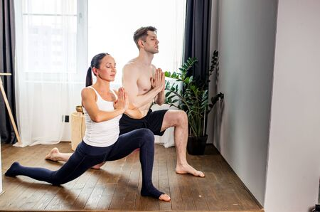 side view on couple keeping balance during yoga exercises, they keep calm while one leg stretched in back 写真素材