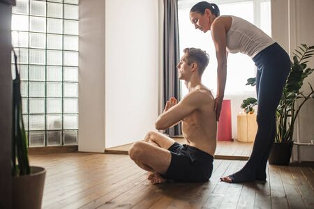 beautiful yogi woman teach man to do exercises, help him to take the right position, indoors. side view