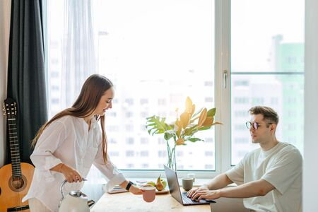 careful caucasian wife going to treat working husband with tasty tea, man work from home, merciful lady pour tea into a cup. freelance work