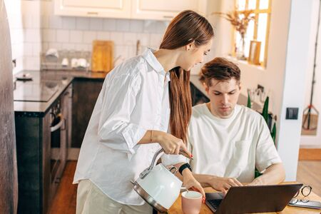 kind caucasian woman treats her husband with tasty tea while he is working from home, using laptop. merciful wife loves husband, support him. freelance, relationships, business at home